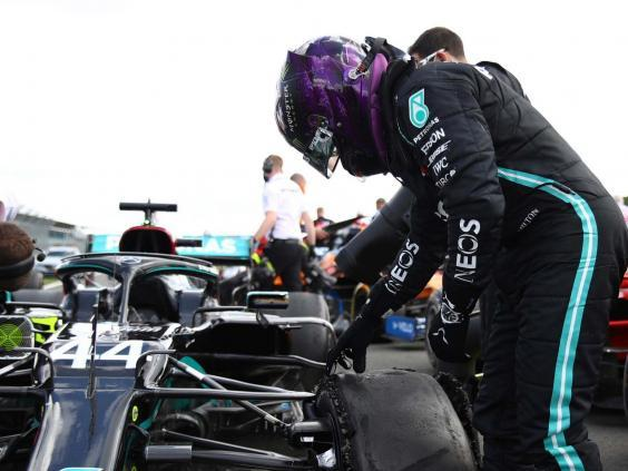 Lewis Hamilton inspects his damaged Mercedes after winning the British Grand Prix (AP)