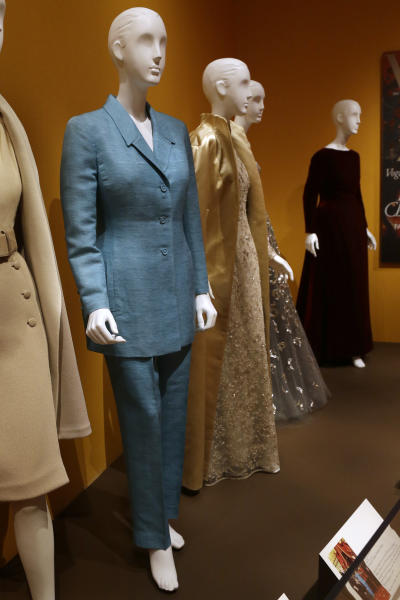 """An Oscar de la Renta pantsuit, left, worn by former first lady Hillary Rodham Clinton, is displayed next to other creations by the designer at the Clinton Presidential Library in Little Rock, Ark., Monday, July8, 2013. The """"Oscar de la Renta: American Icon"""" exhibit is on display at the Clinton library until Dec. 1. (AP Photo/Danny Johnston)"""