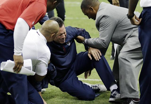 Houston Texans head coach Gary Kubiak, center, his helped after he collapsed on the field during the second quarter of an NFL football game against the Indianapolis Colts, Sunday, Nov. 3, 2013, in Houston. (AP Photo/David J. Phillip)
