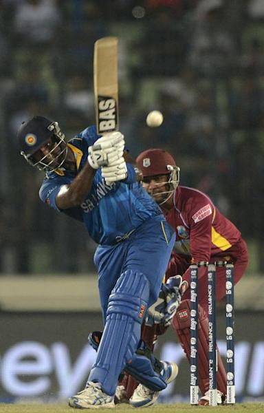 Sri Lankan cricketer Angelo Mathews plays a shot as West Indies wicketkeeper Denesh Ramdin looks on during the Twenty20 World Cup semi-final at The Sher-e-Bangla National Cricket Stadium in Dhaka on April 3, 2014