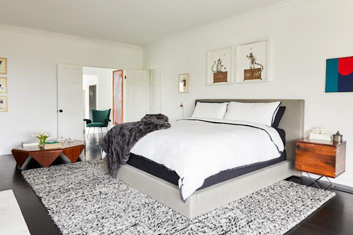 "<div class=""caption""> In the master suite, above the gray linen platform bed from <a href=""https://www.restorationhardware.com/"" rel=""nofollow noopener"" target=""_blank"" data-ylk=""slk:RH"" class=""link rapid-noclick-resp"">RH</a>, we see a diptych by Indian artist Raqib Shaw, known for creating intricate images inlaid with gems. The nightstands are anonymous vintage pieces from Brazil. Behind the double doors is a green lounge chair by Carlo Hauner and Martin Eisler, the lead designers behind <a href=""https://www.r-and-company.com/exhibition/forma/"" rel=""nofollow noopener"" target=""_blank"" data-ylk=""slk:Forma"" class=""link rapid-noclick-resp"">Forma</a>, an influential São Paulo–based furniture company of the midcentury. </div>"