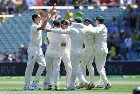 Australia's bowler Pat Cummins (L) celebrates with his teammates after dismissing India's captain Virat Kohli (not pictured) for 3 runs during day one of the first test match between Australia and India at the Adelaide Oval in Adelaide, Australia, December 6, 2018. AAP/Dave Hunt via REUTERS