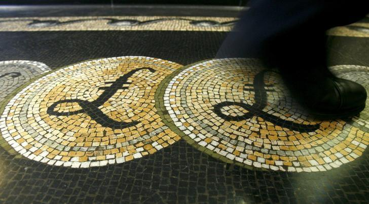 File photograph shows an employee walking over a mosaic depicting pound sterling symbols on the floor of the front hall of the Bank of England in London