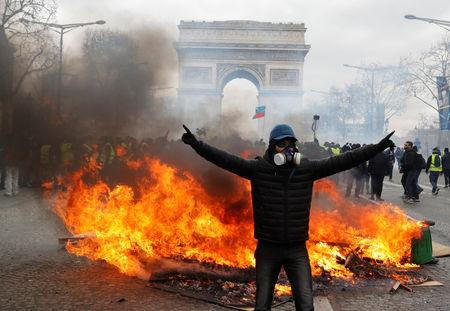 "A protester stands in front of burning barricade during a demonstration by the ""yellow vests"" movement in Paris, France, March 16, 2019. REUTERS/Philippe Wojazer"