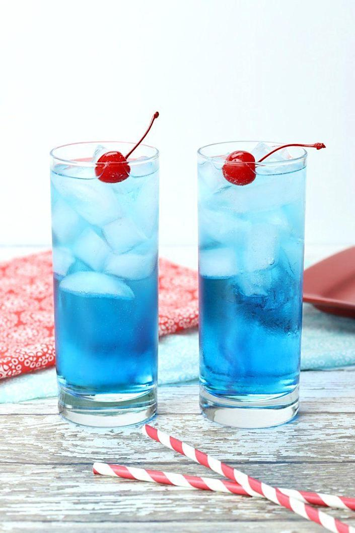 """<p>Blue Curacao, Peach Schnapps, and rum combine to create a brilliant blue drink bursting with bright summer flavors, like lemon and peach. </p><p>Get the <a href=""""https://thetoastykitchen.com/fourth-of-july-cocktail/"""" rel=""""nofollow noopener"""" target=""""_blank"""" data-ylk=""""slk:recipe"""" class=""""link rapid-noclick-resp"""">recipe</a>. </p>"""