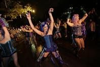 """Members of the Mardi Gras dance group """"The Sirens"""" perform during the Krewe of Orpheus Mardi Gras parade in New Orleans, Monday, Feb. 11, 2013. (AP Photo/Gerald Herbert)"""