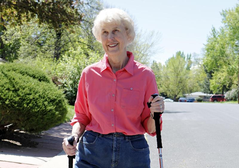 In this photo taken on April 23, 2012, Elaine Vlieger, 79, walks near her home near Denver, Colo. Vlieger is making some concessions to her early stage Alzheimer's, but isn't ready to give up either her home or her independence. She stays active with yard work and daily walks. (AP Photo/Ed Andrieski)