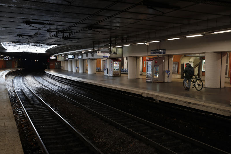 A passenger walks with his bicycle on empty platform of a RER suburb subway, in Paris, Sunday, Dec. 8, 2019 on the fourth day of nationwide strikes that disrupted weekend travel around France. (AP Photo/Francois Mori)