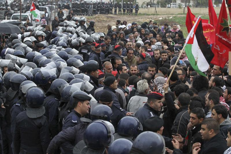 Riot police clash with protesters near the Israeli embassy in Amman