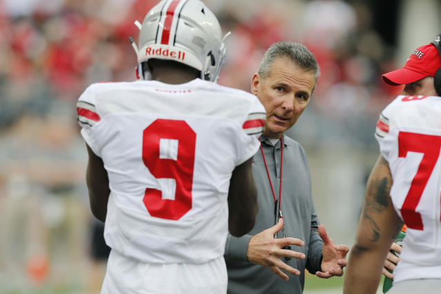 Ohio State head coach Urban Meyer, right, talks with receiver Binjimen Victor during their NCAA college spring football game Saturday, April 14, 2018, in Columbus, Ohio. (AP Photo/Jay LaPrete)