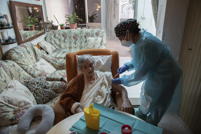 Nurse Pilar Rodríguez administers the COVID-19 vaccine to her patient Antonia Crespi Gomila, 93, at her home in the town of Sa Pobla on the Spanish Balearic Island of Mallorca, Spain, Friday, April 30, 2021. (AP Photo/Francisco Ubilla)