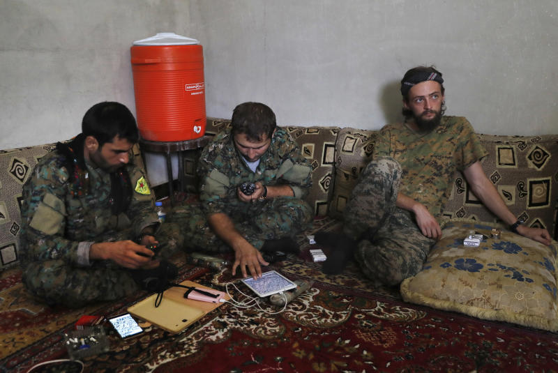 FILE -- In this July 18, 2017 file photo, a British man identified as Jac Holmes, right, who had been fighting with U.S.-backed Syrian Democratic Forces against Islamic State group, sits on the ground next to two Kurdish commanders at a front line base, in the northern city in Raqqa, Syria. Syria's Kurds have been America's partner in fighting the Islamic State group for nearly four years. Now they are furious over an abrupt U.S. troop pull-back that exposes them to a threatened attack by their nemesis, Turkey. The surprise U.S. pull-back from positions near the Turkish border, which began Monday, Oct. 7, 2019, stung even more because the Kurds have been abandoned before by the U.S. and other international allies on whose support they'd pinned their aspirations.. (AP Photo/Hussein Malla, File)