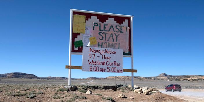 A sign asking Navajo residents to stay safe and warning of a curfew near the Navajo Nation town of Casamero Lake in New Mexico on May 20, 2020.