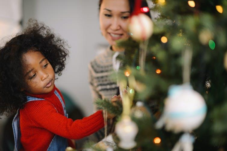 Child and mother decorate Christmas tree.