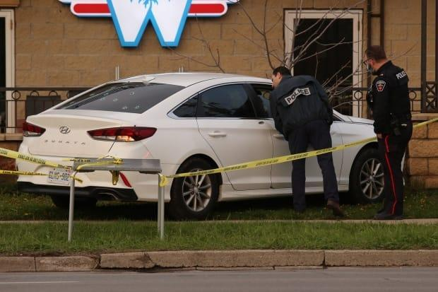 Durham police officers look at a white car that appears to have been fired upon in Ajax on Wednesday.