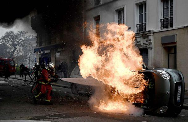 PHOTO: A firefighter tries to extinguish a burning car on place d'Italie in Paris on November 16, 2019, on the sidelines of a demonstration of the 'yellow vest' (gilets jaunes) marking the first anniversary of the movement. (Philippe Lopez/AFP via Getty Images)