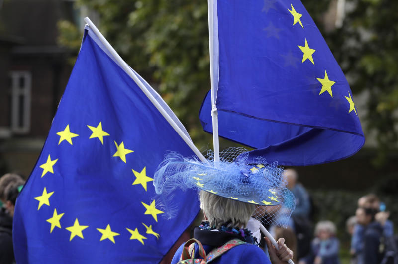 An Anti-Brexit demonstrator waves European Union flags near Parliament in London, Tuesday, Oct. 8, 2019. The British government said Tuesday that the chances of a Brexit deal with the European Union were fading fast, as the two sides remained unwilling to shift from their entrenched positions. (AP Photo/Kirsty Wigglesworth)