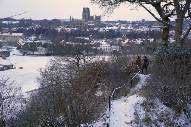 People take pictures from Pelaw Wood of a snow-covered Durham Cathedral