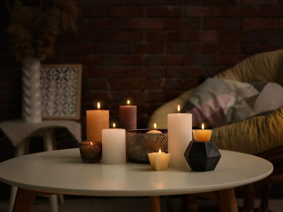 Bunch of candles in a dimly-lit living room.