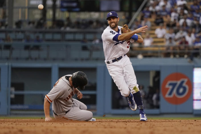 Los Angeles Dodgers shortstop Chris Taylor, right, throws to first base after forcing out San Francisco Giants' Alex Dickerson, left, at second base on a ground ball by Donovan Solano during the second inning of a baseball game Thursday, July 22, 2021, in Los Angeles. Solano was safe at first. (AP Photo/Marcio Jose Sanchez)