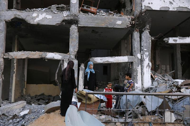 Palestinians stand in front of what used to be their home in a building complex that was destroyed by fighting between Hamas Militants and Israel on August 29, 2014 in the northern Gaza Strip city of Beit Hanun (AFP Photo/Roberto Schmidt)
