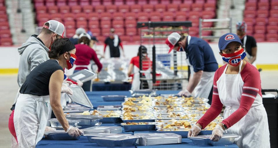 """<span class=""""caption"""">Volunteers prepare meals for food banks on the floor of the Bell Centre in Montréal in May 2020 at the height of the COVID-19 pandemic. </span> <span class=""""attribution""""><span class=""""source"""">THE CANADIAN PRESS/Ryan Remiorz</span></span>"""