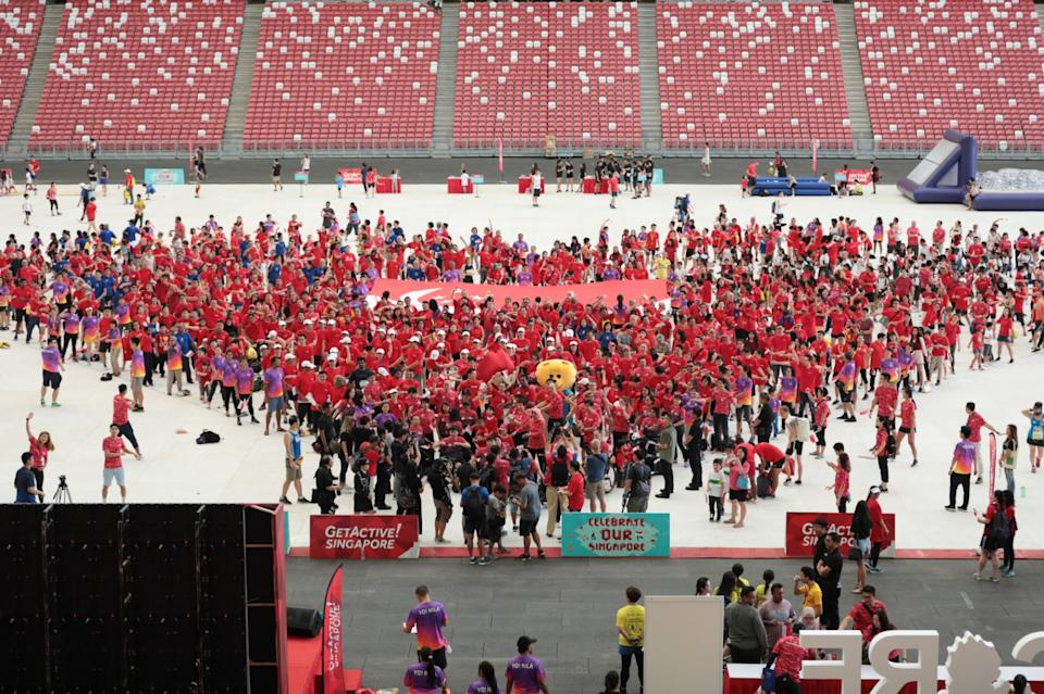 Volunteers and partners of the Get Active! Singapore sport fiesta form a heart formation with President Halimah Yacob and MCCY minister Grace Fu at the National Stadium (PHOTO: Sport Singapore)