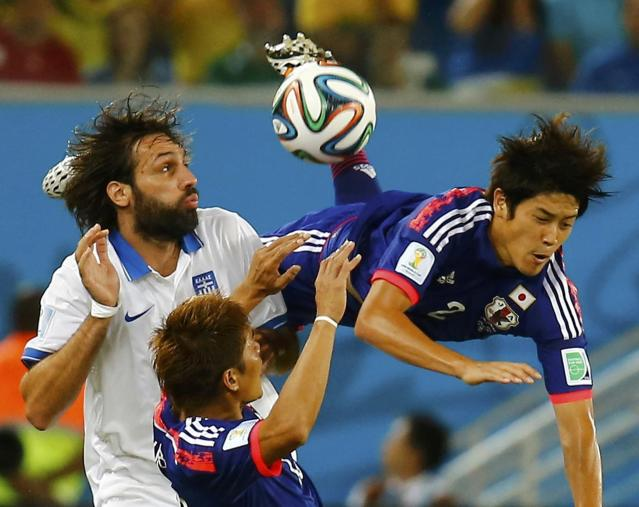 Japan's Atsuto Uchida (R) is fouled by Greece's Giorgios Samaras (L) during their 2014 World Cup Group C soccer match at the Dunas arena in Natal June 19, 2014. REUTERS/Kai Pfaffenbach (BRAZIL - Tags: SOCCER SPORT WORLD CUP TPX IMAGES OF THE DAY)