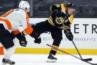 Boston Bruins' Brad Marchand (63) takes a shot against Philadelphia Flyers' Robert Hagg (8) during the second period of an NHL hockey game, Saturday, Jan. 23, 2021, in Boston. (AP Photo/Michael Dwyer)