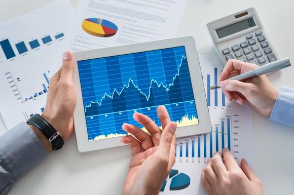 Two pairs of hands holding a tablet with a graph and a pen hovering over it