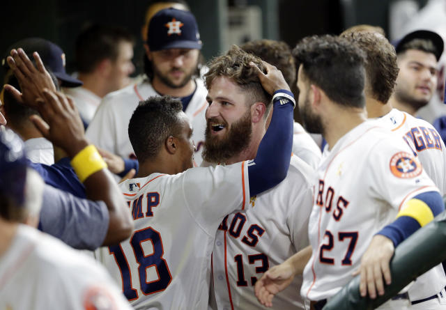 Houston Astros' Tony Kemp (18) ruffles the hair of designated hitter Tyler White in the dugout after he scored their sixth run against the Los Angeles Angels during the eighth inning of a baseball game, Saturday, Sep. 1, 2018, in Houston. White's two-run RBI double earlier in the inning put the Astros ahead. (AP Photo/Michael Wyke)