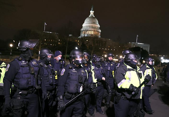 Police officers in riot gear monitor protesters gathering at the U.S. Capitol on Jan. 6 in Washington.