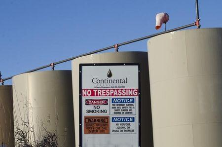 Storage tanks stand on a Continental Resources oil production site near Williston