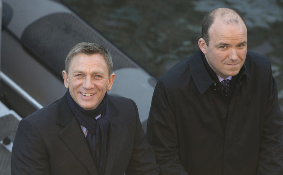 """FILE - In this Tuesday, Dec. 16, 2014 file photo, actors Daniel Craig, left, and Rory Kinnear smile for photographers as they film a scene for the new James Bond film, Spectre, in London. 007 star Daniel Craig and the film's other luminaries will be at the October world premiere of the new James Bond film """"Spectre"""", and Palace officials said Wednesday Sept. 16, 2015, they will be joined on the red carpet by Prince William and his wife Kate and Prince Harry. (AP Photo/Alastair Grant, File)"""