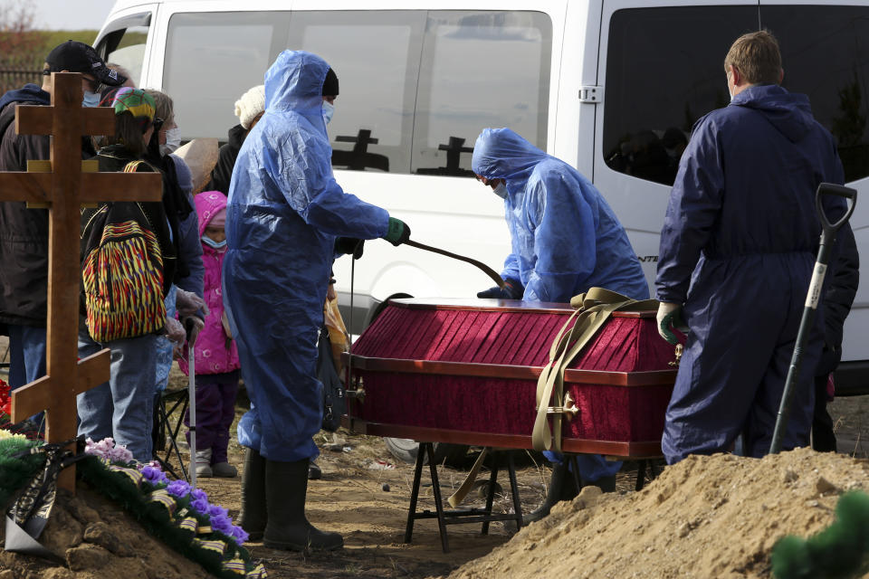 Grave diggers wearing protective suits disinfect a coffin of a COVID-19 victim for burial at a cemetery outside Omsk, Russia, Thursday, Oct. 7, 2021. Russia's daily coronavirus infections have soared to their highest level so far this year as authorities have struggled to control a surge in new cases amid a slow pace in vaccinations and few restrictions in place. The daily coronavirus death toll topped 900 for a second straight day with 924 new deaths reported Thursday. Russia already has Europe's highest death toll in the pandemic and a conservative way of calculating the number suggests the actual number could be even higher. (AP Photo)