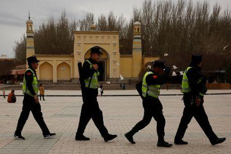 A police patrol walk in front of the Id Kah Mosque in the old city of Kashgar