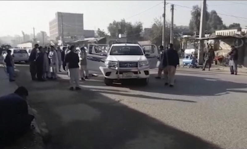In this image made from video, locals inspect the site of a gun attack on a Japanese aid worker's truck Wednesday, Dec. 4, 2019, Nangarhar province, easter Afghanistan. Japanese physician and aid worker Tetsu Nakamura has died of his wounds after an attack that also killed five Afghans, including the doctor's bodyguards, the driver and a passenger. (AP Photo)