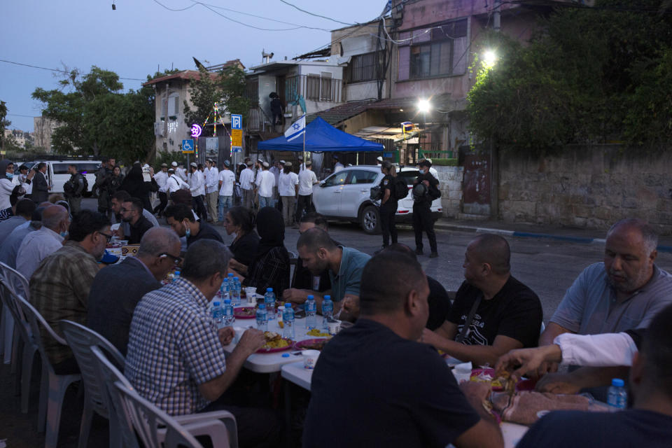 Israeli police stand guard as Palestinian Muslims break their fast during the holy month of Ramadan and Jewish settlers gather to begin Shabbat at a Palestinian house occupied by settlers, in the Sheikh Jarrah neighborhood of east Jerusalem, Friday, May 7, 2021. Dozens of Palestinian families in east Jerusalem are at risk of losing their homes to Jewish settler groups following a decades-long legal battle. The threatened evictions have sparked weeks of protests and clashes in recent days, adding to the tensions in Jerusalem. (AP Photo/Maya Alleruzzo)