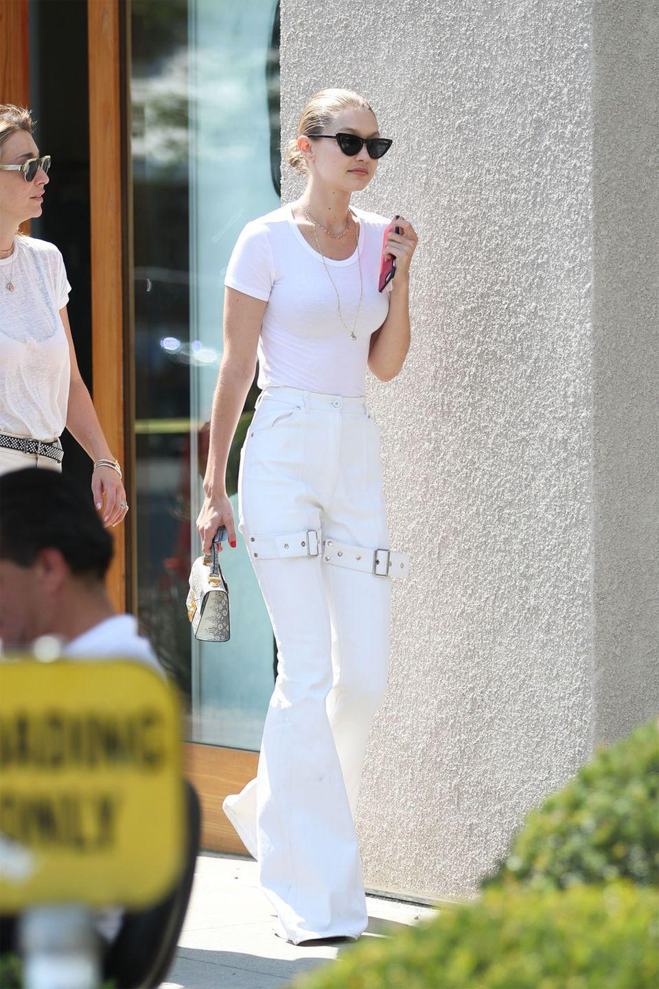 <p>In a white t-shirt, matching bellbottom pants, Le Specs cat-eye sunglasses and holding a STALVEY purse while out in West Hollywood. </p>