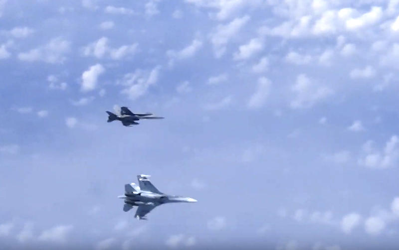 In this video grab taken from a footage on Aug. 13, 2019, and distributed by Russian Defense Ministry Press Service, a Russian air force's Su-27 fighter jet, bottom, maneuvers to ward off a NATO F-18 warplane over the Baltic Sea.  A video aired on Russian state television shows a fighter jet warding off a NATO military aircraft that approached a passenger plane carrying Russia's defense minister Sergei Shoigu. (Russian Defense Ministry Press Service via AP)