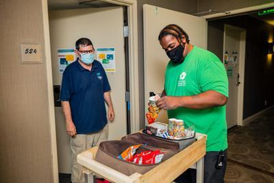 Chrysalis client and National Health Foundation staff member Paul serving snacks to guests at NHF's Project Roomkey site.