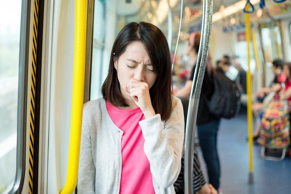 Woman coughing on the bus