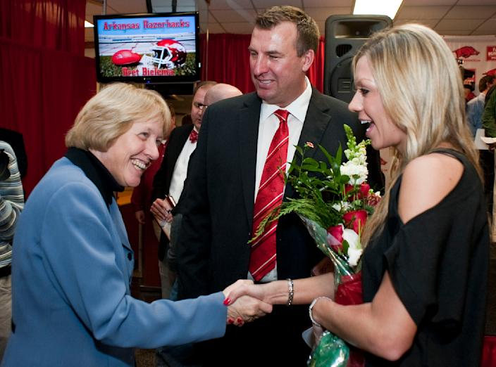 Arkansas associate athletic director Bev Lewis, left, shakes hands Jen Bielema, right, as new head coach Bret Bielema, center, stands by following an NCAA college football news conference in Fayetteville, Ark., Wednesday, Dec. 5, 2012. Bielema, who will be paid $3.2 million annually for six years, replaces interim coach John L. Smith, who was hired after Bobby Petrino was fired in April. (AP Photo/April L. Brown)