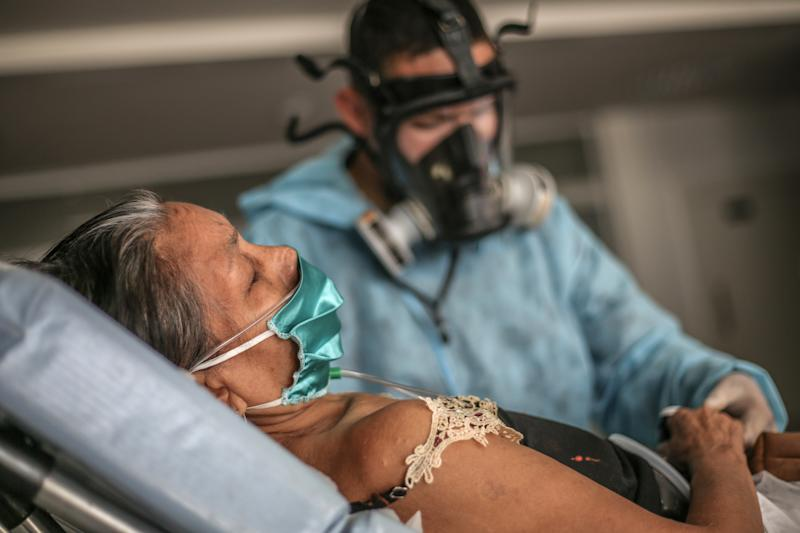 MANAUS, BRAZIL - MAY 27: A nurse checks vital signs of a woman infected by coronavirus (COVID-19) as she arrives at the Gilberto Novaes Municipal Field Hospital on May 27, 2020 in Manaus, Brazil. According to World Health Organization (WHO), Brazil has now 374,898 confirmed cases of COVID-19 with 23,473 deaths. (Photo by Andre Coelho/Getty Images)