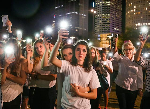 <p>Mary Claire Foley, center left, 16, embraces Ariana Skafidas, 16, students at Henry B. Plant High School at Curtis Hixon Park in downtown Tampa, Fla., Monday, Feb. 19, 2018, as they raise their lights during a vigil to honor victims of Wednesday's shooting at Marjory Stoneman Douglas High School in Parkland, Fla. (Photo: Dirk Shadd/Tampa Bay Times via AP) </p>