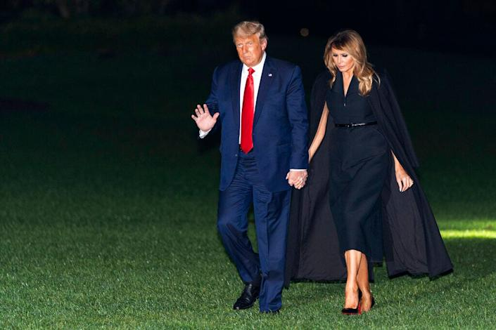 President Donald Trump, accompanied by first lady Melania Trump, waves as he walks from Marine One on the South Lawn of the White House early on Oct. 23, 2020. Trump is returning from a debate in Nashville, Tennessee.