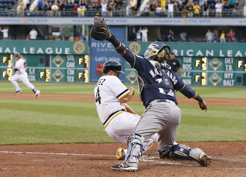Milwaukee Brewers catcher Martin Maldonado, right, reaches for the throw as Pittsburgh Pirates' Gaby Sanchez, left, scores from third on a pinch-hit by Russell Martin in the fourteenth inning of the baseball game on Sunday, June 30, 2013, in Pittsburgh. The Pirates won 2-1, in 14 innings. (AP Photo/Keith Srakocic)
