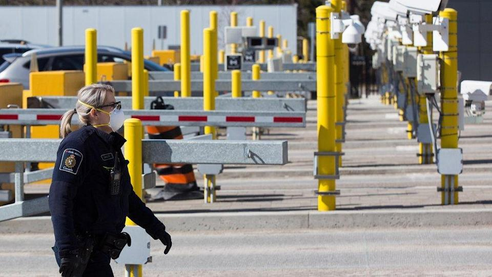 A Canadian border officer wears as face mask at the US/Canada border in Lansdowne, Ontario, on March 22, 2020.
