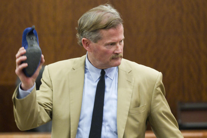 Defense attorney Jack Carroll holds evidence in the case, a blue suede shoe, as he gives his closing argument in the trial against Ana Trujillo, Tuesday, April 8, 2014, in Houston. Trujillo, 45, was found guilty of fatally stabbing her boyfriend with the stiletto heel of her shoe, hitting him at least 25 times in the face. (AP Photo/Houston Chronicle, Brett Coomer)