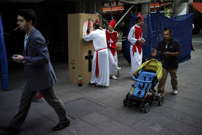 Spaniards dressed up like Bishops for a stag party play the role of a confessor in downtown Madrid, Saturday June 9 2012. Spain will ask for a bank bailout from the eurozone, becoming the fourth and largest country to seek help since the single currency bloc's debt crisis erupted.(AP Photo/Daniel Ochoa de Olza)